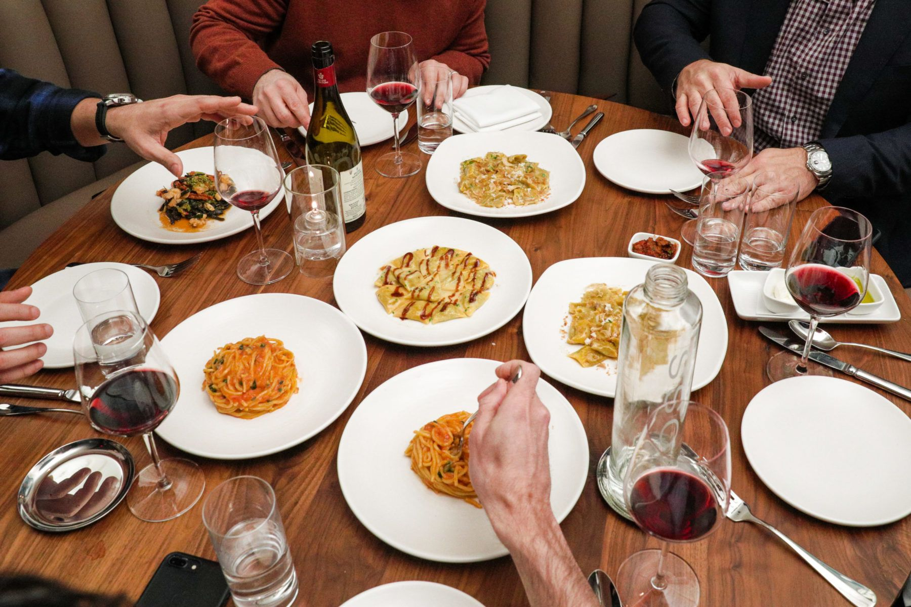 Table with plates of spaghetti, wine and people eating.