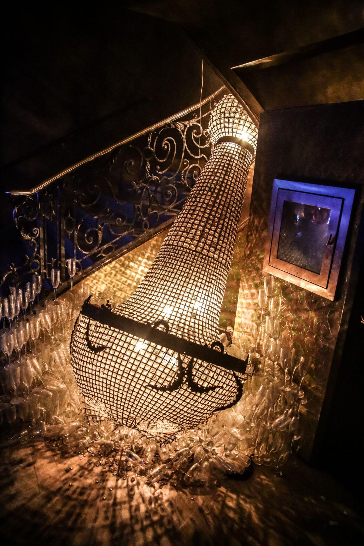 Chandelier on the floor near staircase at Diamond Horseshoe