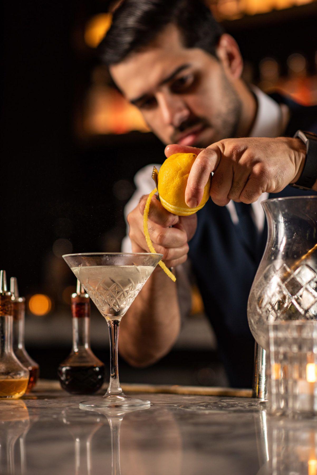 Bartender peeling lemon over a martini glass at bar