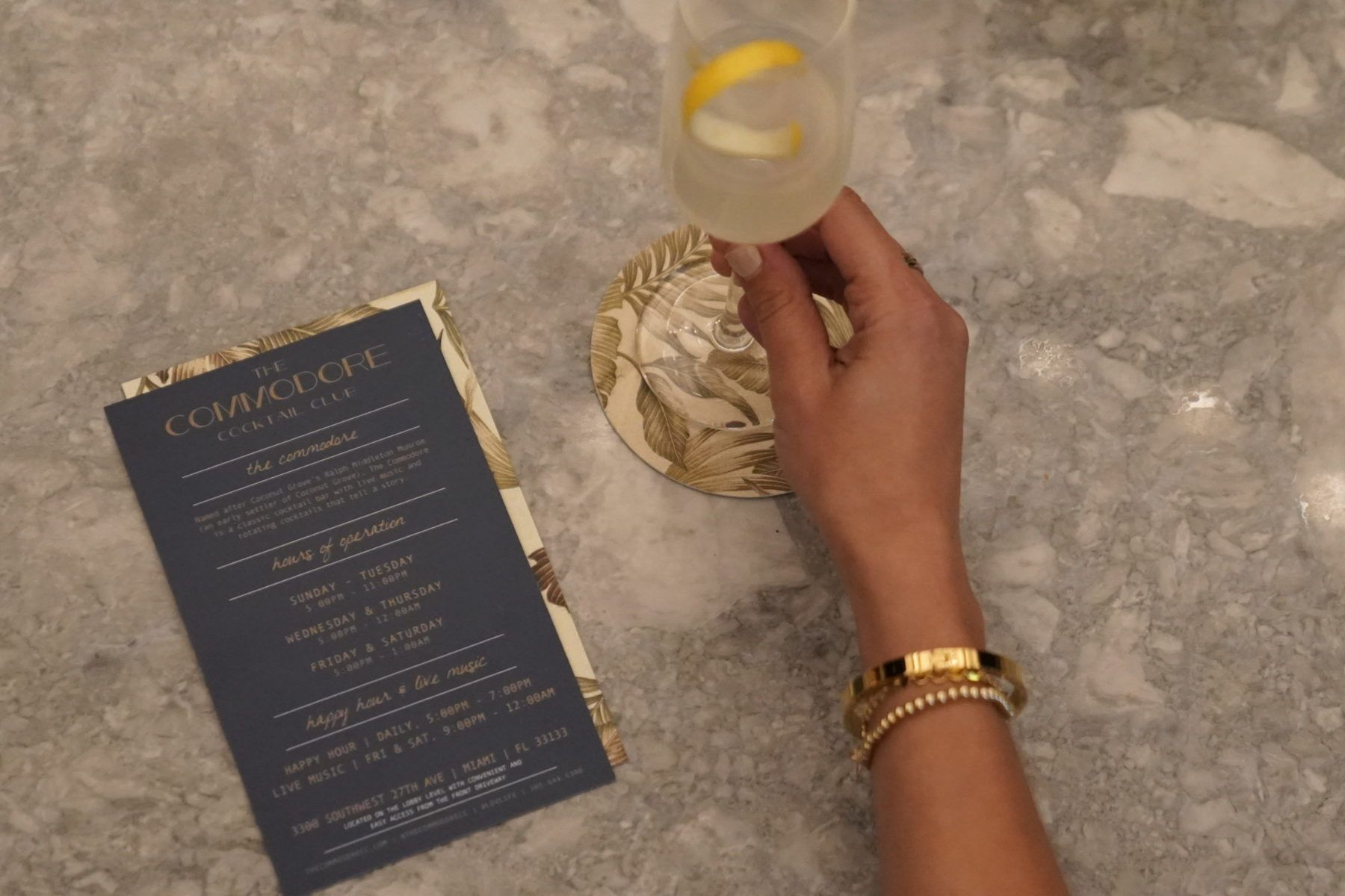 Hand holding champagne class on marble bar top