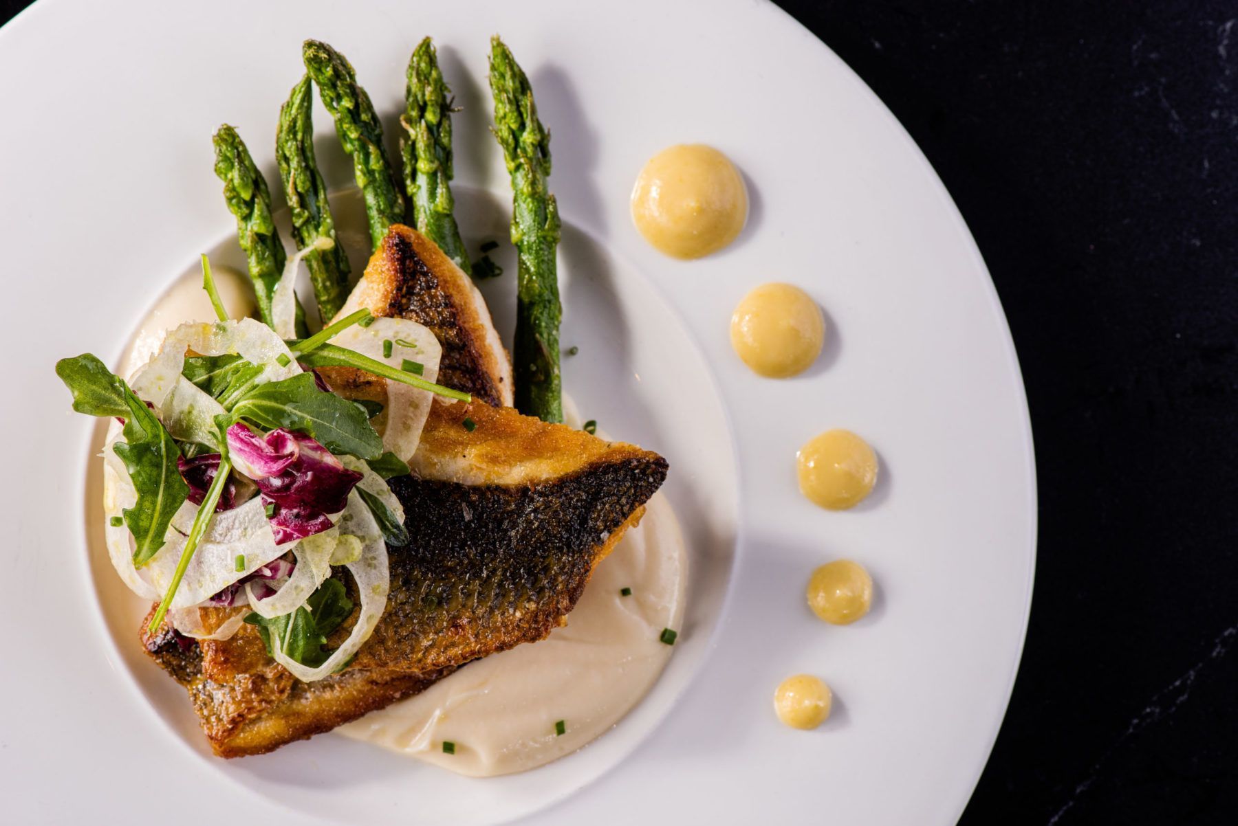 Branzino on a plate with asparagus