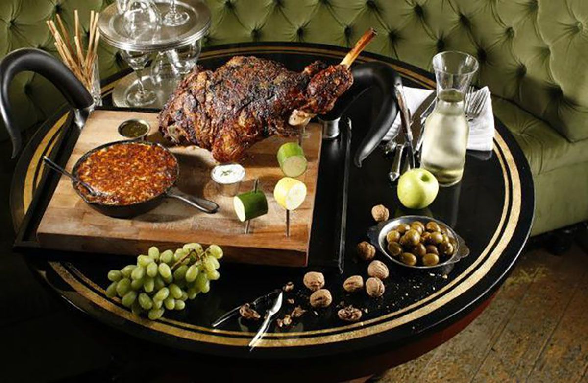 Dinner table with olives, nuts, wine, grapes and large steak