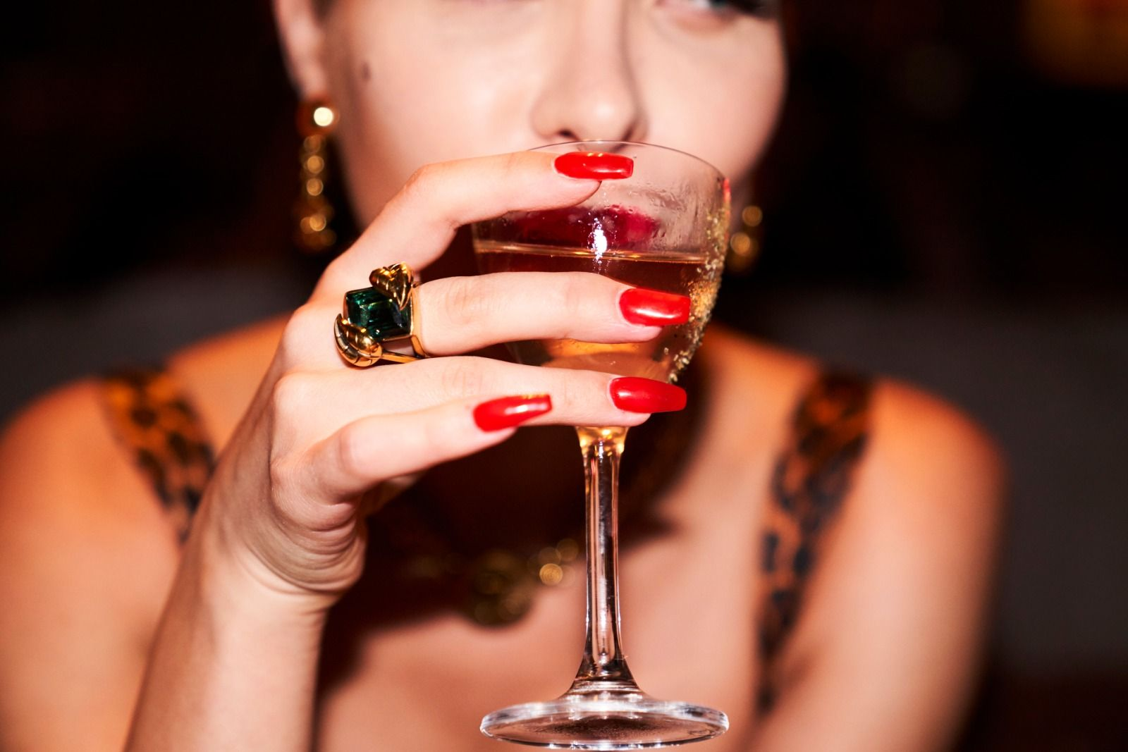 Girl with red nails drinking a cocktail