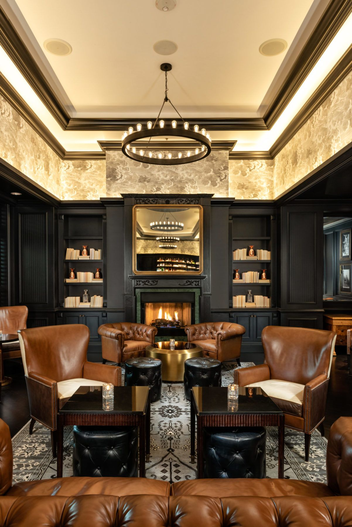 Fireplace view, dark wood and leather couches at The Commodore