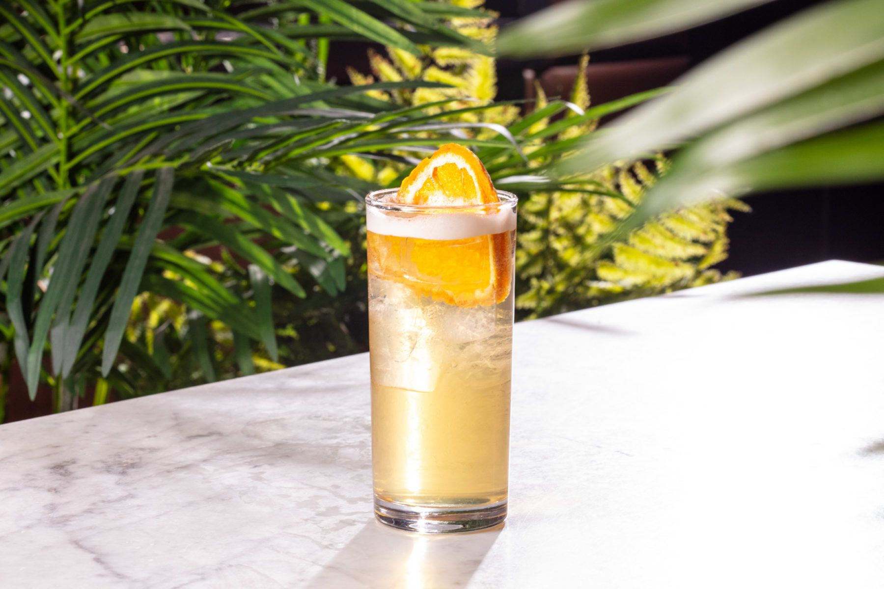 Organge cocktail with palm tree background