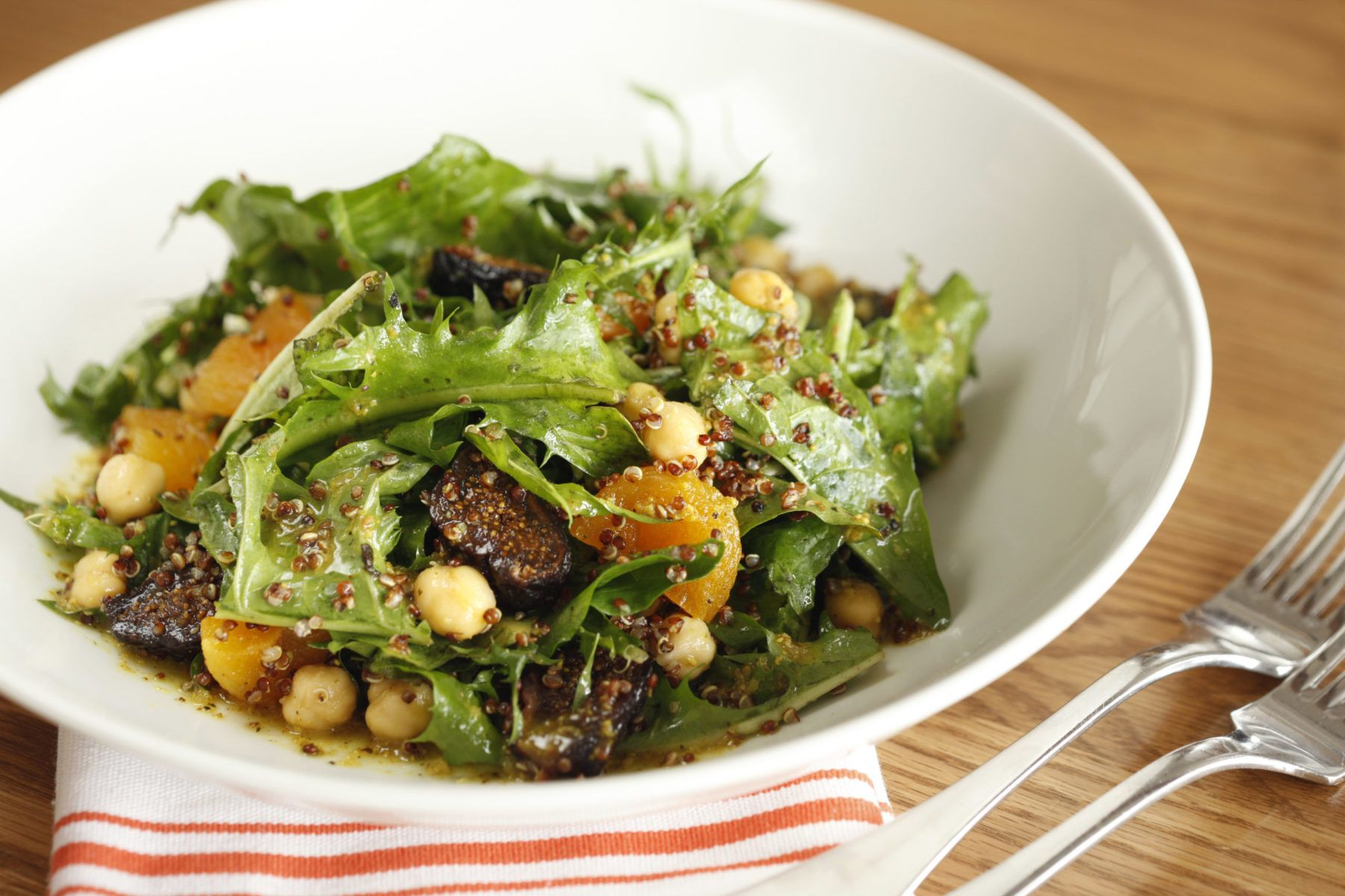 Salad and quinoa in bowl on dinner table