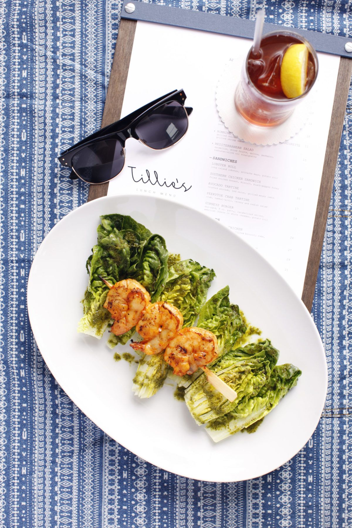 Shrimp and salad on a plate with sunglasses and a cocktail on the table