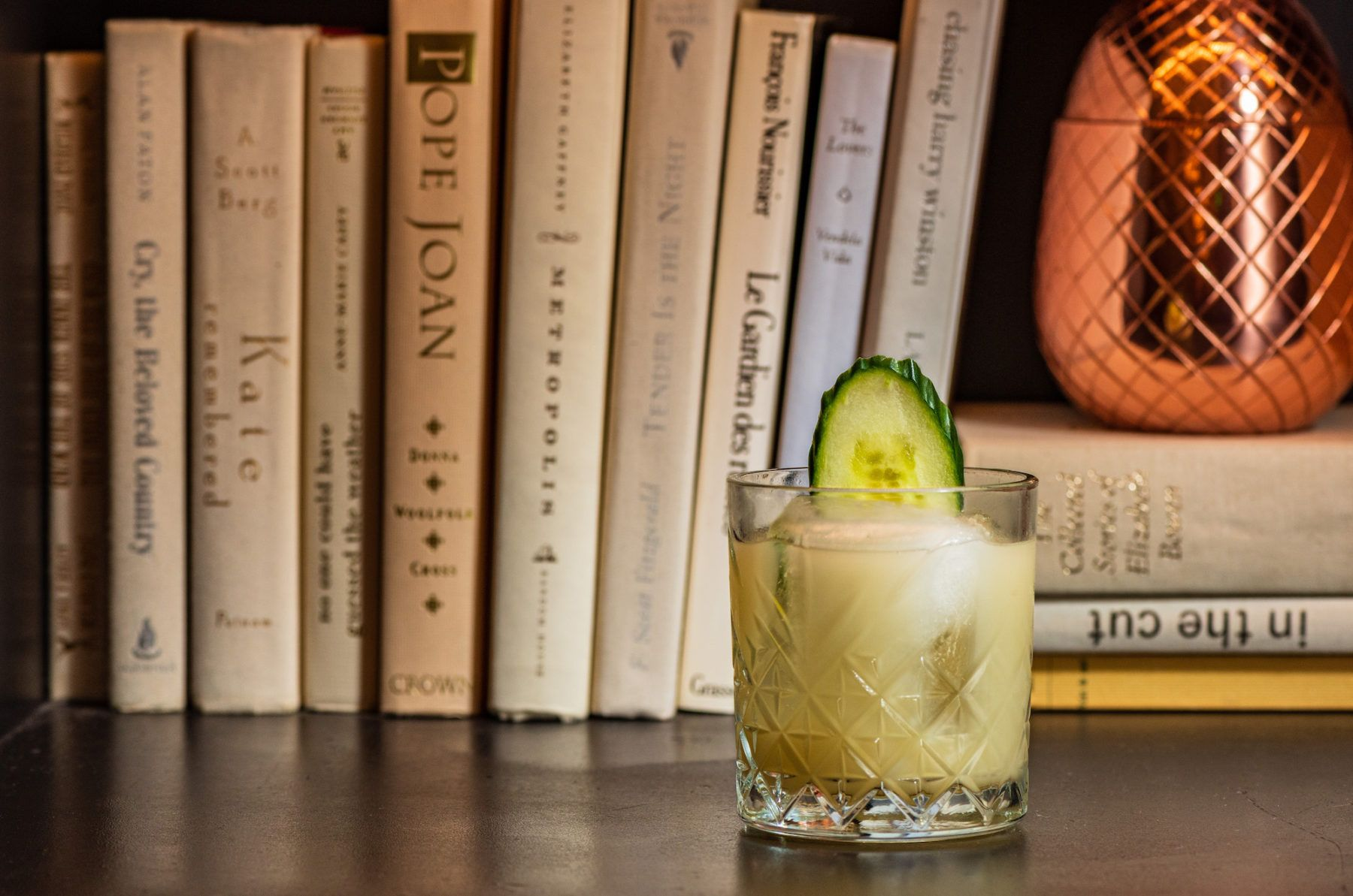 Cocktail in crystal glass on book shelf