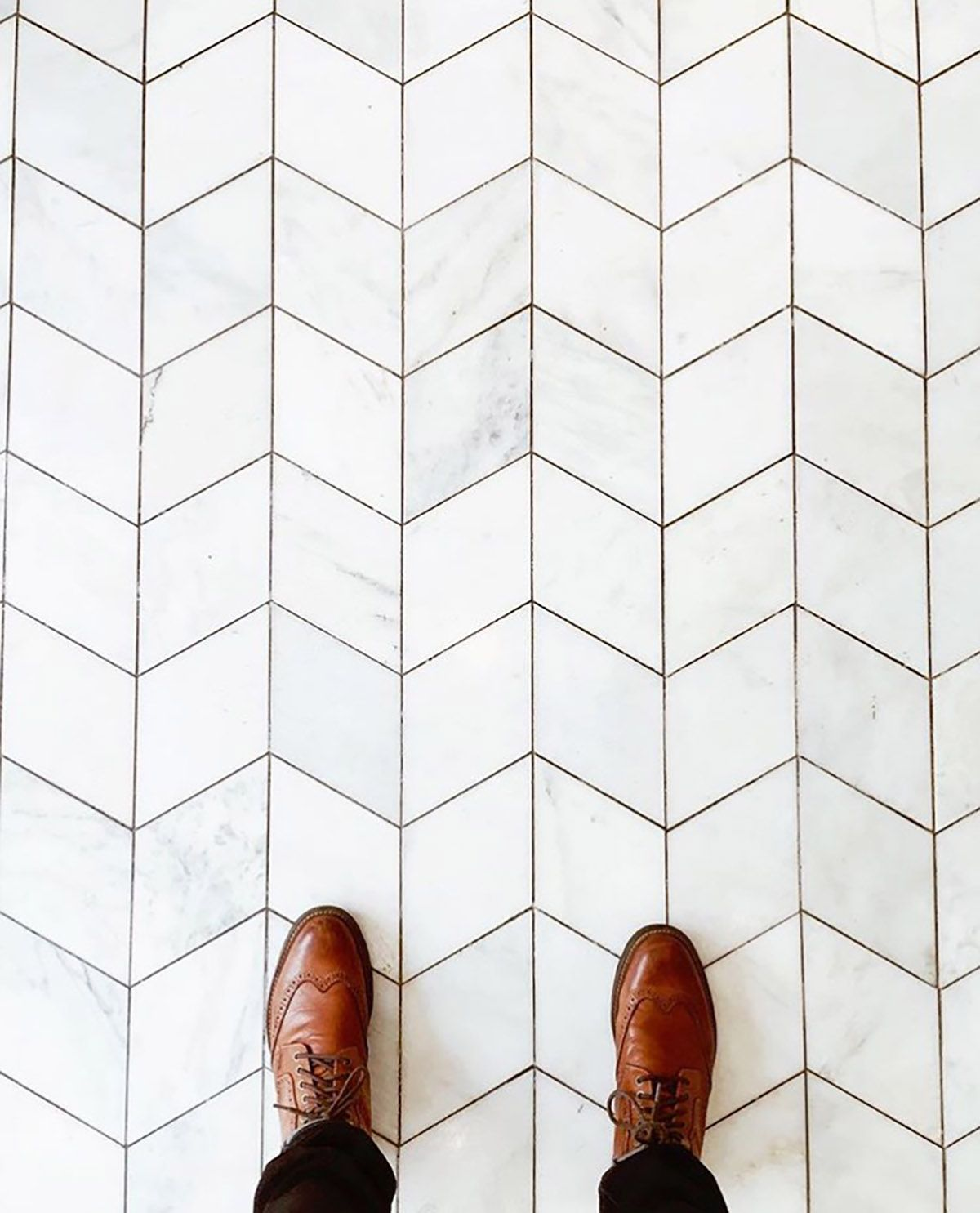 man standing with brown shoes on a marble floor at Corso