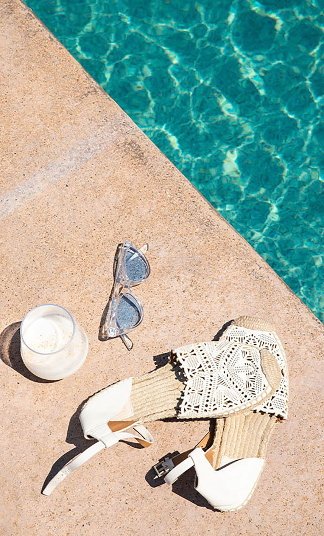 sunglasses and frozen drink next to the pool